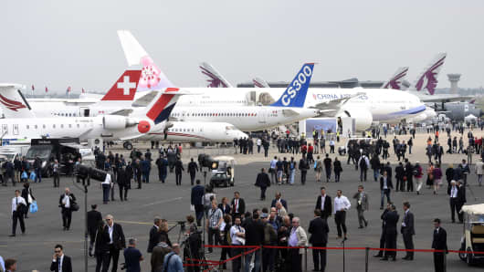 People walk amongst aircraft exhibited on the tarmac during the opening of the International Paris Airshow at Le Bourget on June 15, 2015.