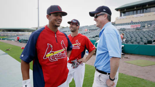 In this Feb. 25, 2013, file photo, Houston Astros general manager Jeff Luhnow, right, talks to St. Louis Cardinals center fielder Jon Jay, left, and second baseman Daniel Descalso before an exhibition spring training baseball game in Jupiter, Fla.