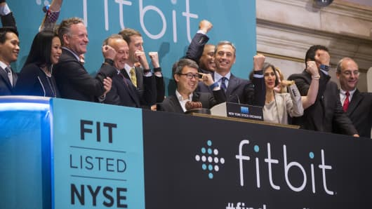 James Park (C), Fitbit CEO, stands as company officials applaud after ringing the opening bell on the day of the company's IPO at the New York Stock Exchange, June 18, 2015.
