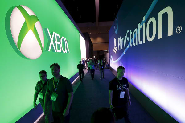 Attendees walk past Microsoft Xbox and Sony PlayStation signs at the Electronic Entertainment Expo (E3) in Los Angeles, June 16, 2015.