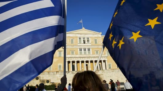 A woman waves a Greek national flag and a European Union flag during a rally outside the parliament, in Athens June 18, 2015.