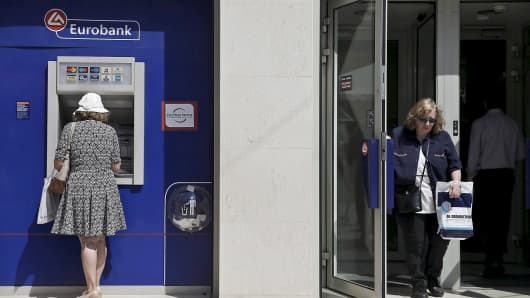 A woman makes a transaction at an ATM outside a Eurobank branch as another woman exits the bank in Athens, Greece, June 15, 2015.