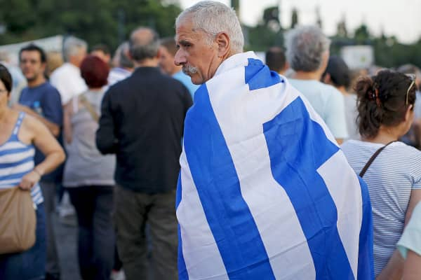 A man wears a Greek flag during a pro-government rally calling on Greece's European and International Monetary creditors to soften their stance in the cash-for-reforms talks in Athens, Greece, June 17, 2015.