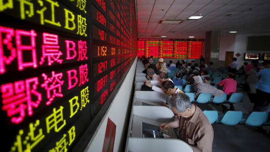 Investors look at computer screens showing stock information at a brokerage house in Shanghai.