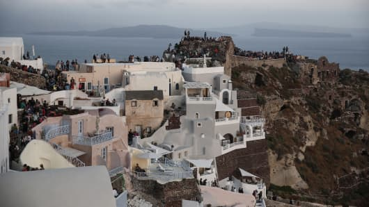 Tourists gather on viewing positions to watch the sun set in Oia village on the island of Santorini, Greece, in May 2015.