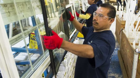 An employee builds a window at the Thompson Creek Window factory in Landover, Md.