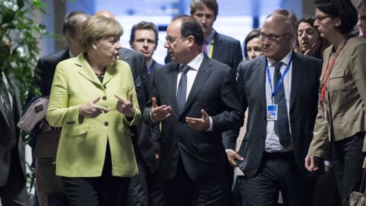 Angela Merkel (L) talks with French President Francois Hollande after their bilateral meeting during a Eurozone emergency summit on Greece in Brussels, Belgium, June 22, 2015.