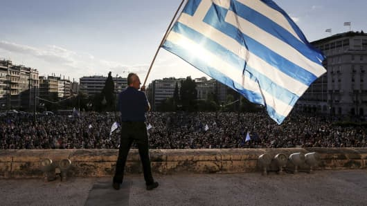 A man waves a Greek national flag while standing at the premises of the parliament building during a rally in front of the parliament building calling on the government to clinch a deal with its international creditors and secure Greece's future in the Eurozone, in Athens, Greece, June 22, 2015.
