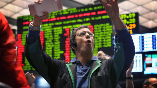A trader signals offers in the Standard & Poor's 500 stock index futures pit at the CME Group in Chicago.