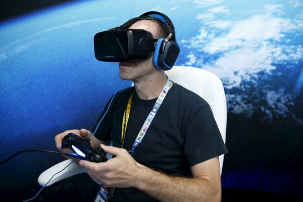 A man wears an Oculus VR headset as he plays a video game at the Electronic Entertainment Expo in Los Angeles, June 16, 2015.