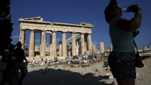 A woman takes a drink in front of the Parthenon temple on Acropolis hill in Athens, June 18, 2015.