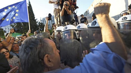 Pro-European Union protesters scuffle with riot police outside the parliament building during a rally in Athens, June 22, 2015.