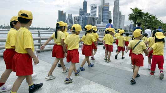 Singapore pre-school children walk along the Singapore River waterfront.