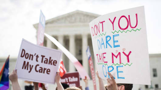 Affordable Care Act supporters hold up signs outside the Supreme Court as they wait for the court's decision on Obamacare on Thursday, June 25, 2015.