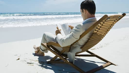 Busnessman reading book at the beach