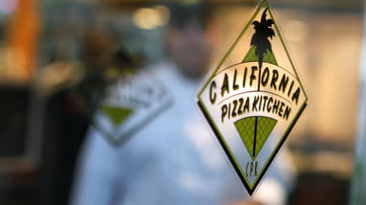 A chef walks towards the entrance of a California Pizza Kitchen Inc. restaurant in New York.