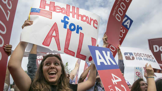 Supporters of the Affordable Care Act celebrate as the opinion for health care is reported outside of the Supreme Court in Washington, D.C., on June 25, 2015.