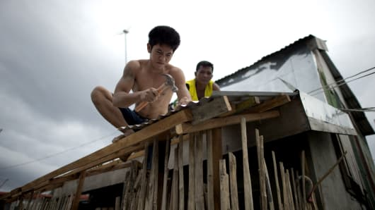 Workers reinforce the roof of a house at the port area in Manila, the Philippines.