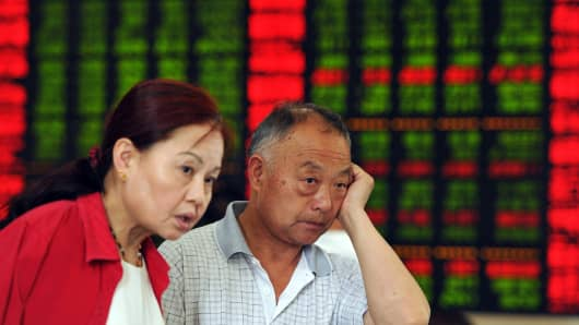 Chinese stock investors react as they check share prices at a securities firm in Fuyang, in China's Anhui province.