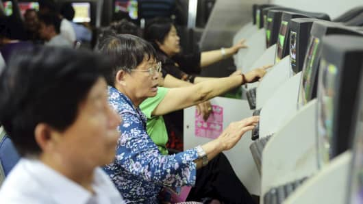 Investors look at computer screens showing stock information at a brokerage house in Qingdao, Shandong province, China.