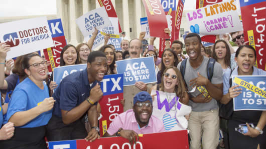 Affordable Care Act supporters cheer in front of the Supreme Court after the court decided that the ACA may provide nationwide tax subsidies, June 25, 2015, in Washington.