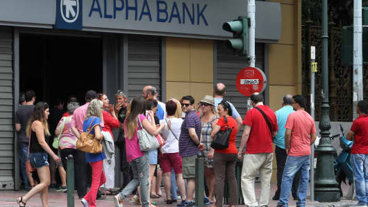 People wait in a queue in front of a bank's ATM to withdraw their cash in Athens, Greece on June 28, 2015. Greeks are anxious about whether the European Central Bank will increase the emergency liquidity assistance, banks can draw on from the country's central bank or not.