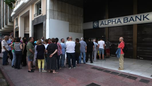 People wait in a queue in front of a bank's ATM to withdraw their cash in Athens, Greece on June 28, 2015.