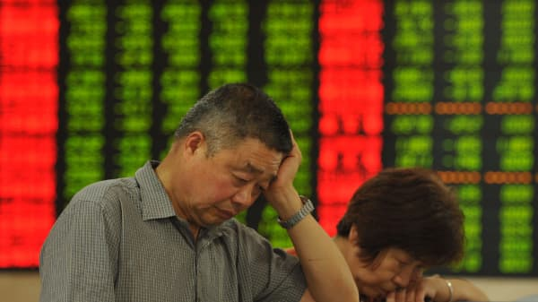 Investors observe the stock market at a stock exchange hall in Fuyang, Anhui province of China.