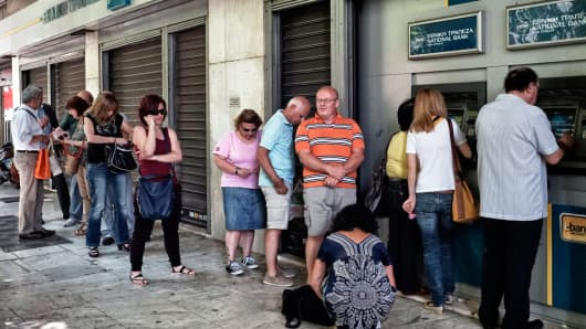 People wait in line to withdraw 60 euros from an ATM after Greece closed its banks on June 29, 2015 in Athens, Greece.