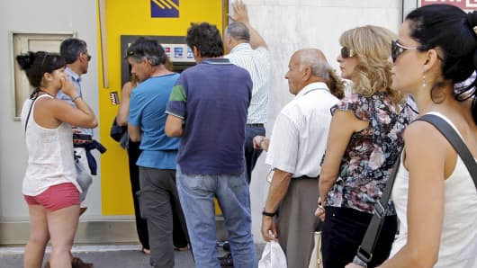 People line up to withdraw cash from an automated teller machine (ATM) outside a Piraeus Bank branch in Iraklio on the island of Crete, Greece June 28, 2015.