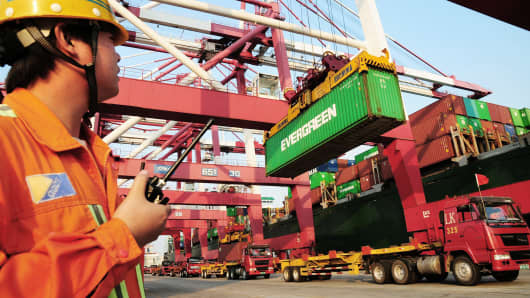 A worker monitors the loading of containers onto a ship at the harbor in Qingdao, China.
