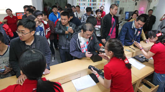 Customers wait in line to buy the Xiaomi Mi Note Pro in Zhengzhou, China, on May 12, 2015.