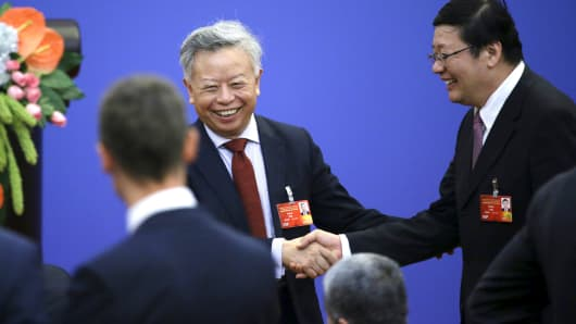 Jin Liqun, left, current secretary general of the Multilateral Interim Secretariat of Asian Infrastructure Investment Bank, shakes hands with China's Finance Minister Lou Jiwei ahead of a signing ceremony of articles of agreement of the AIIB, at the Great Hall of the People in Beijing, June 29, 2