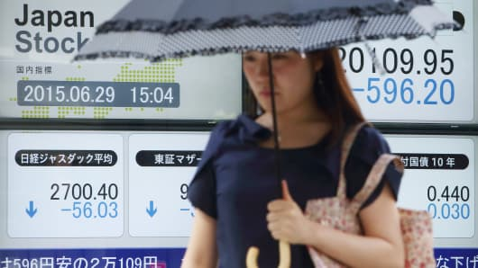 A pedestrian walks past an electronic stock board displaying the Nikkei 225 Stock Average, top right, outside a securities firm in Tokyo, June 29, 2015.