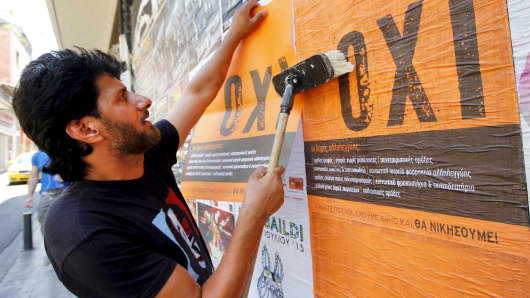 "A man puts up posters with the word ""No"" in Greek in Athens, July 1, 2015."