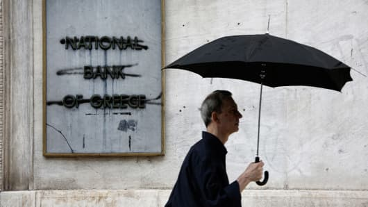 A pedestrian passes a graffiti damaged sign at the entrance to a main branch of the National Bank of Greece in Thessaloniki, Greece, on Wednesday, July 1, 2015.