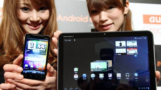 Models for KDDI Corp. pose with a Motorola XOOM tablet device manufactured by Motorola mobility Inc.