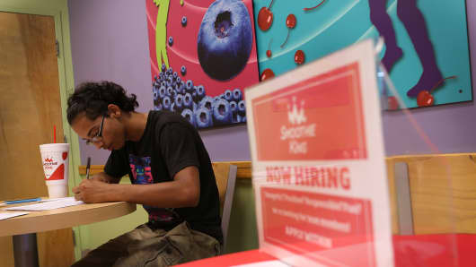A new employee fills out paperwork as he starts his new job at Smoothe King in Miami, Florida.