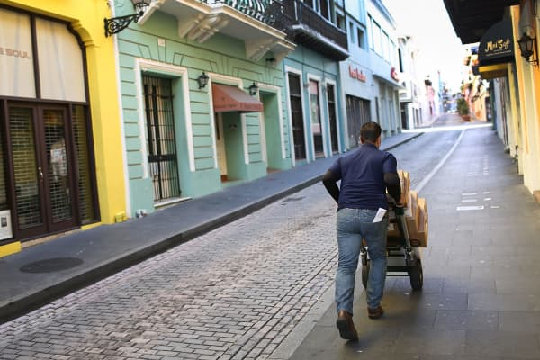 A delivery man pushes a cart through a street of San Juan, Puerto Rico.