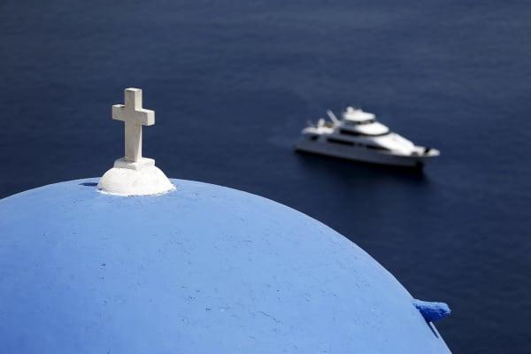 A yacht is seen below the village of Oia on the Greek island of Santorini, Greece, July 1, 2015.