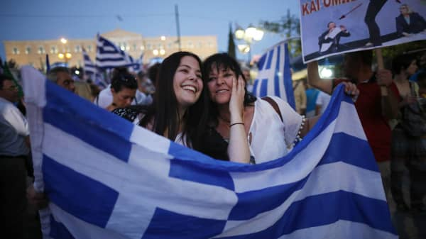 People celebrate in front of the Greek parliament as early opinion polls predict a win for the Oxi, or No, campaign in the Greek aus