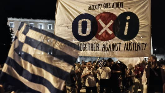People celebrate in front of the Greek parliament as Greek voters vote 'No' in the austerity referendum on July 5, 2015.
