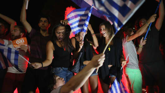 People celebrate in front of the Greek parliament as the people of Greece reject the debt bailout by creditors.
