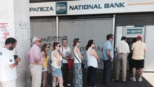 Greeks queue to use a National Bank of Greece ATM in Athens.