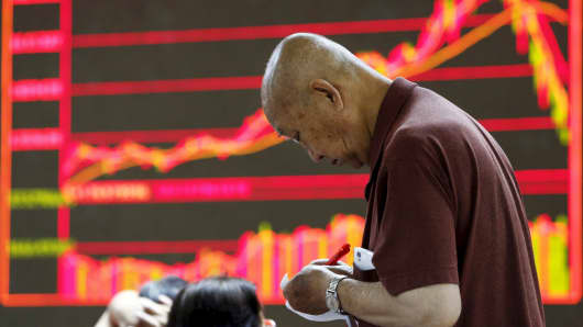 An investor takes notes in front of an electronic board showing stock information at a brokerage office in Beijing, China, July 7, 2015.