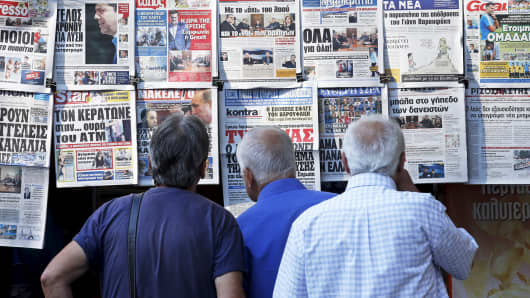 People read the front pages of various newspapers hanging at a kiosk in central Athens, Greece, July 7, 2015.