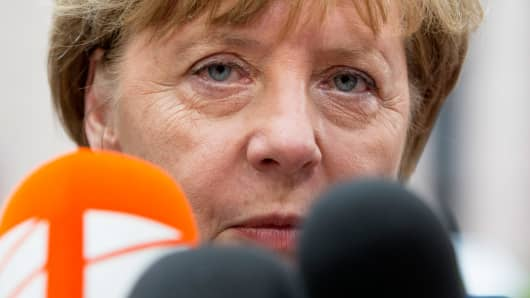 Angela Merkel, Germany's chancellor, speaks to members of the media while arriving for an emergency Greek summit with European leaders in Brussels, Belgium, on Tuesday, July 7, 2015.
