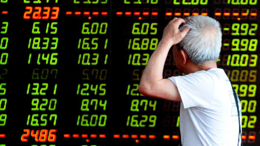 An investor observes an electronic board at a stock exchange hall on July 7, 2015 in Shenyang, China.