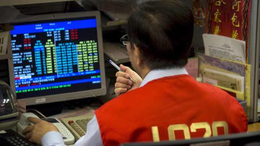 A floor trader checks share prices at the Hong Kong Exchange in Hong Kong.