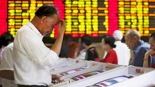 Investors look at computer screens showing stock information at a brokerage house in Shanghai, China.
